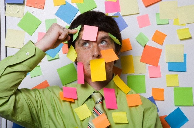 Male office worker covered with sticky notes --- Image by © Big Cheese Photo/Corbis